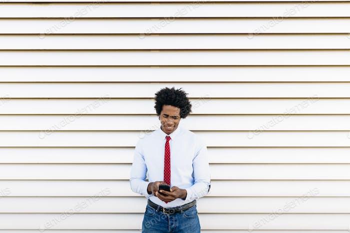 Hombre de negocios negro usando un teléfono inteligente con un fondo de persianas blancas