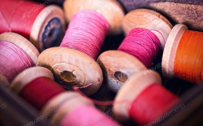 Sammlung von roten Spulen Fäden in einer Grunge Holzkiste angeordnet
