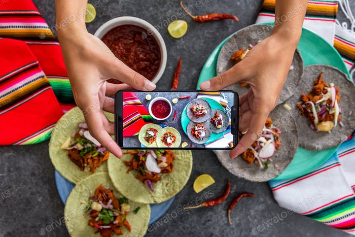 Person photographing some mexican food arrange on a table