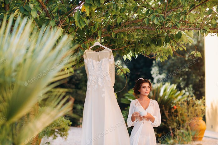 a beautiful bride stands next to a wedding dress with a Cup of tea in a boudoir outfit next to a