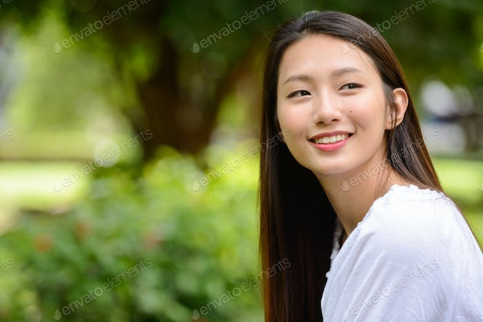 Happy young beautiful Asian teenage girl thinking at the park