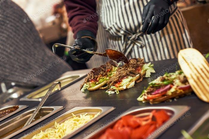 A chef preparing a sandwich with fresh salad. Food cort of street fair