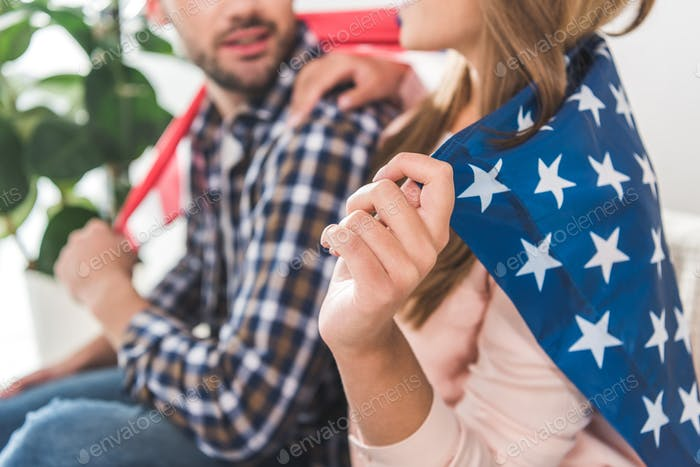Cropped shot of young attractive couple wrapped in American flag