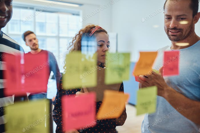 Group of designers brainstorming with notes on a glass wall