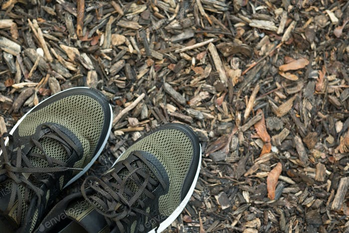 Pair of man sport shoes on wood chips texture background