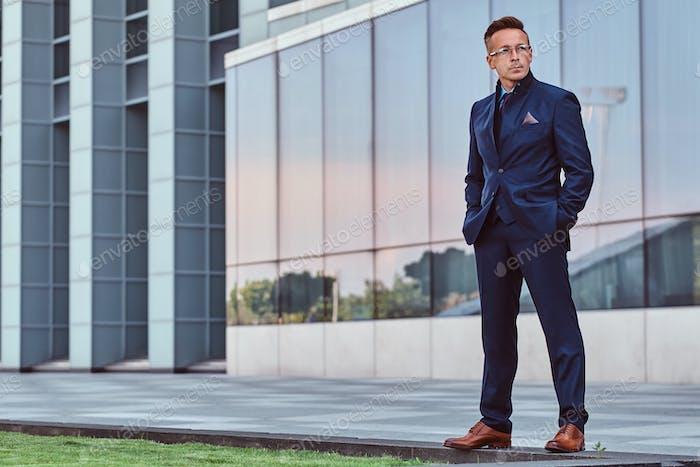 Selbstbewusster Geschäftsmann in einem eleganten Anzug gekleidet, der draußen vor dem Hintergrund der Stadtlandschaft steht.