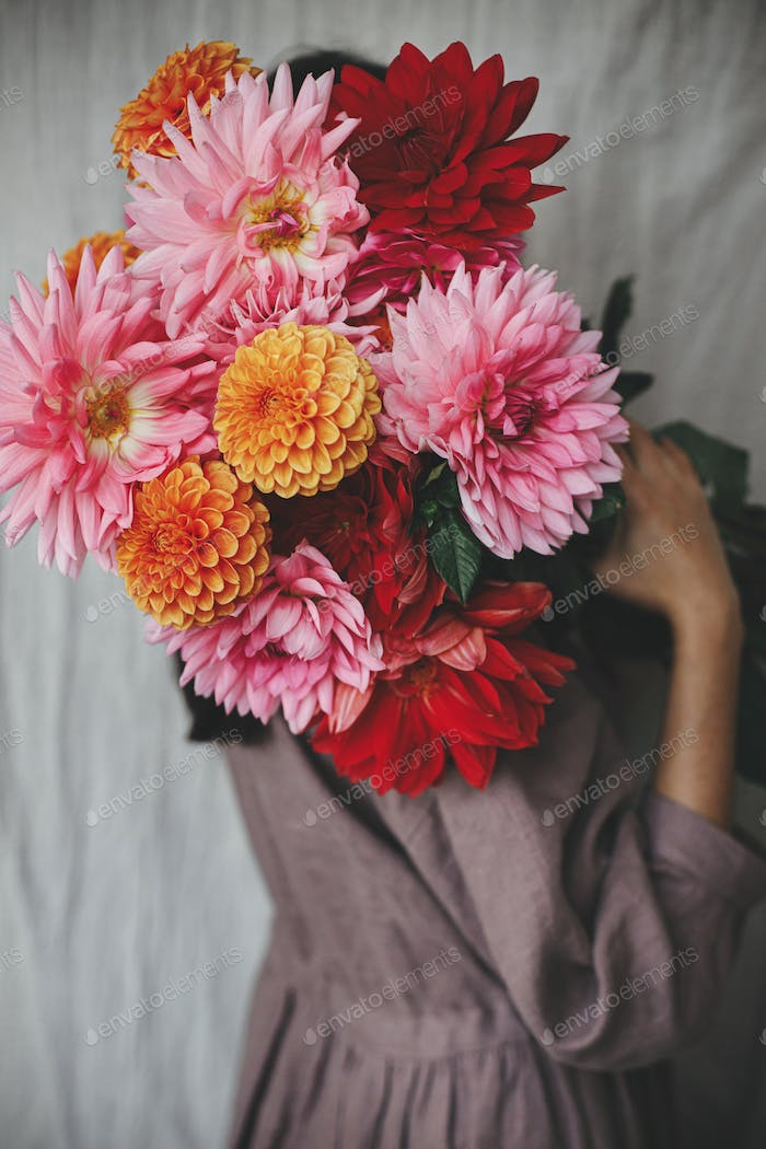 Beautiful woman holding dahlias in rustic room.  Florist in linen dress hiding behind autumn flowers