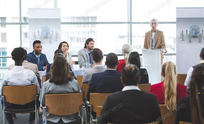 Female speaker speaking in business seminar in modern office building
