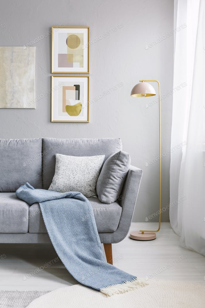 Real photo of a grey couch with pillows and blanket standing nex