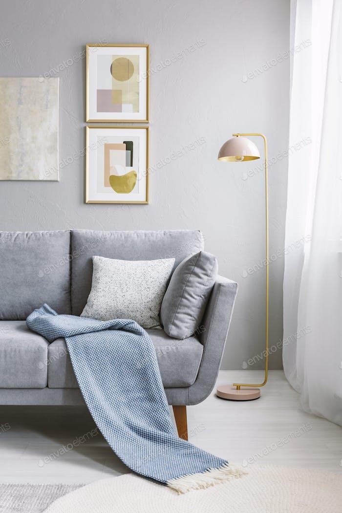 Echtes Foto einer grauen Couch mit Kissen und Decke stehend nex