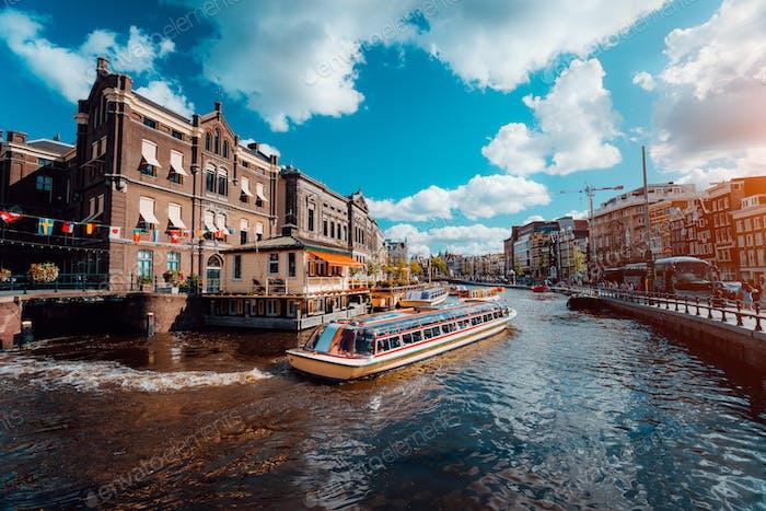 Ausflugsboot auf dem Fluss Amstel. Stadtbild von Amsterdam Niederlande. Erstaunlich bewölkt bei sonnigem Wetter