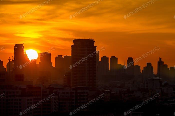 Closeup silhouette Bangkok cityscape at sunrise time with lens flare, worm color tone