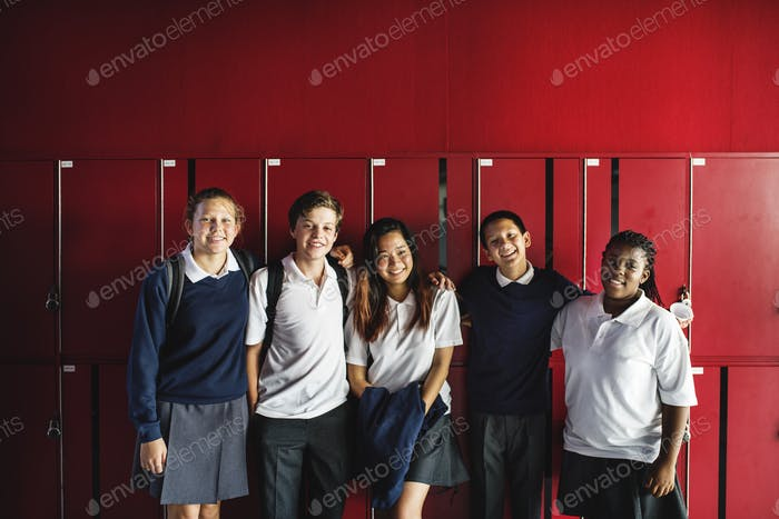 Friends standing together in front of lockers