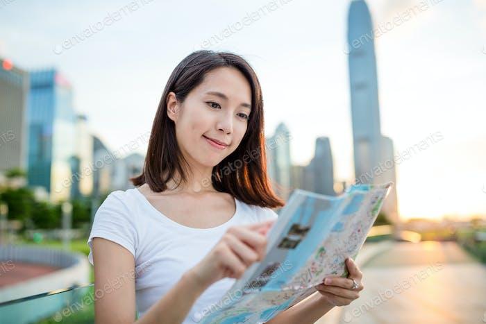 Woman looking at city map in Hong Kong