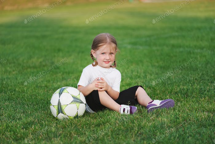 little happy girl on football field