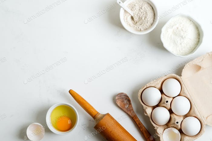 Baking ingredients for making homemade traditional bread or cakes on a light grey marble background