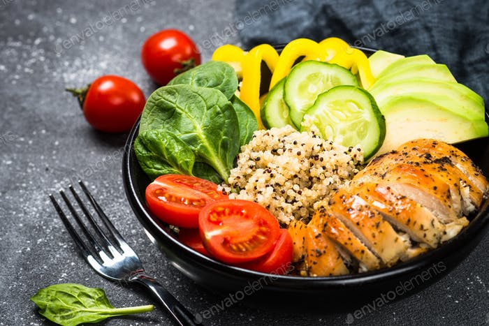 Buddha bowl quinoa salad with chicken and vegetables on black
