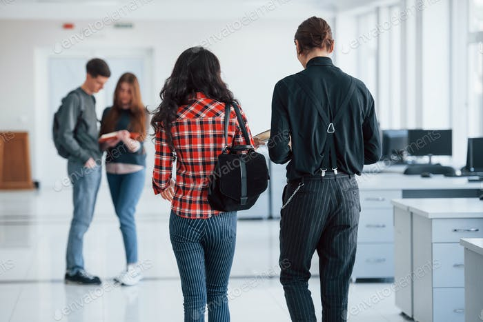 Two couples. Group of young people walking in the office at their break time