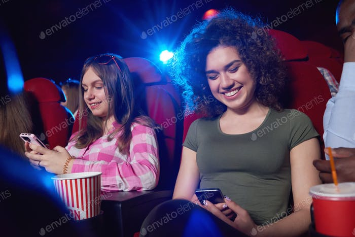 Young woman using smart phone at the cinema