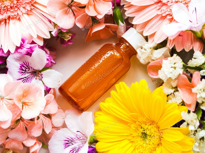 Skin care serum in orange bottle with flowers