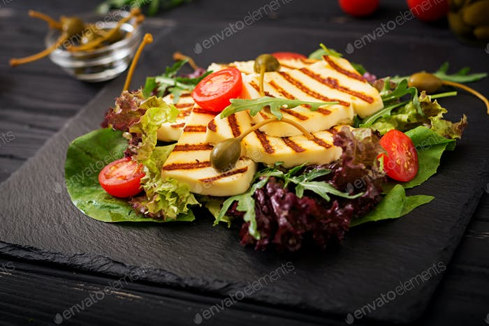 Fresh salad with grilled cheese, tomatoes, capers, lettuce and arugula.