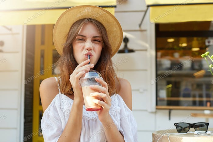 woman wears stylish summer hat and white dress, making funny face and drinking milkshake