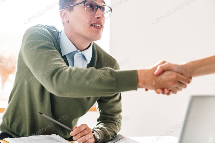 Pleased young guy shaking hand of his colleague.