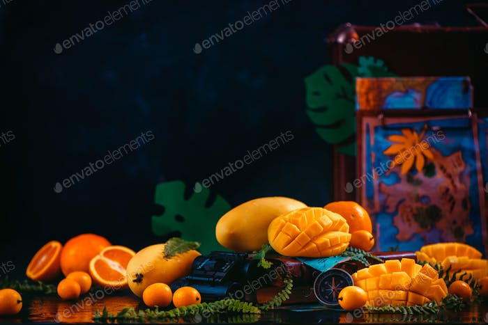 Mango, oranges, kumquat and other tropical fruits on a dark background with copy space. Traveling