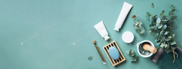 White cosmetic bottles, eucalyptus flowers, towels, soap on green background. Top view, flat lay