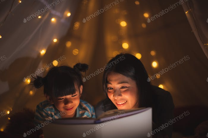 young Asian mother read the story in the book for her daughter children on the bed at home
