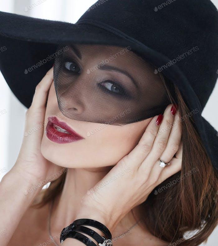 Portrait of stylish woman in a black hat.