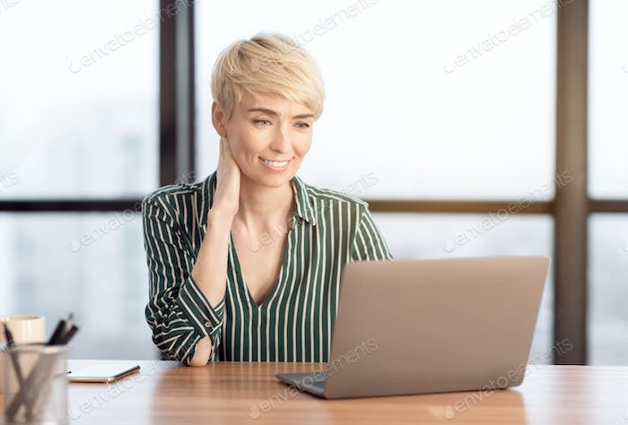 Mature Businesswoman At Laptop Working In Modern Office