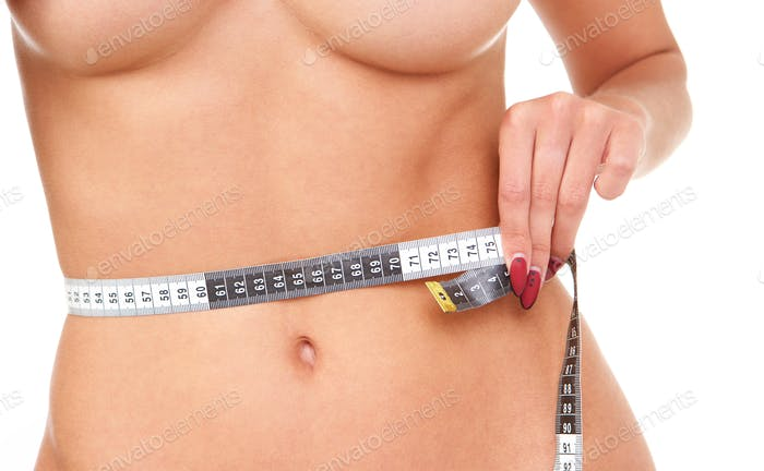 Close up woman standing and measuring waistline with tape