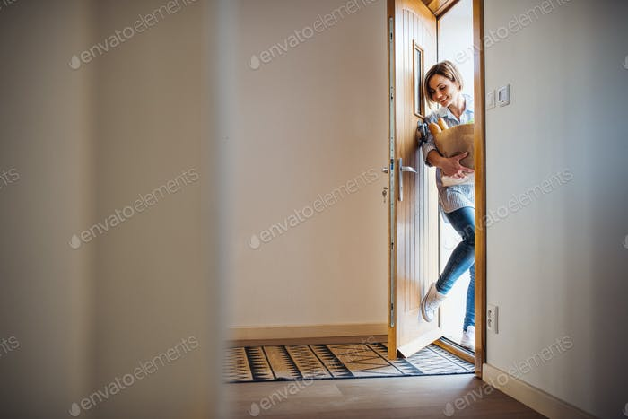 A young woman with groceries in paper shopping bag walking in through front door.