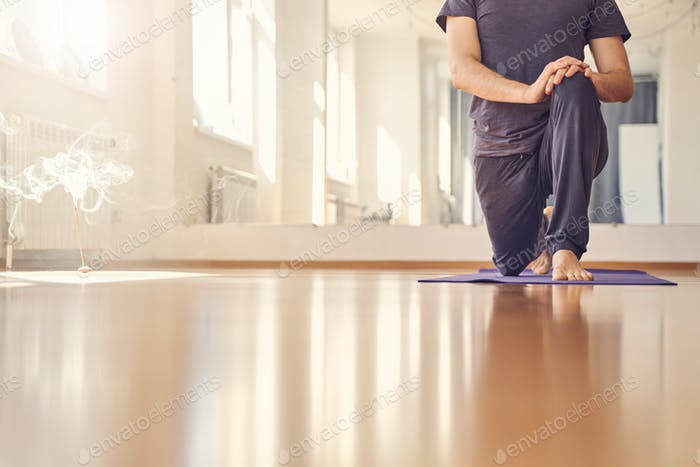 Young man standing in yoga position on yoga mat