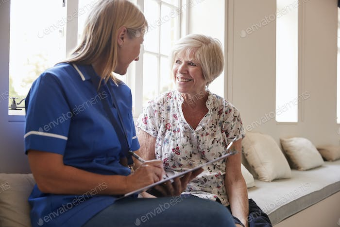 Senior woman sits with nurse making notes at retirement home