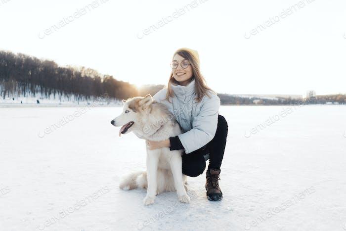 Glückliche junge Mädchen spielen mit sibirischen Husky Hund im Winterpark