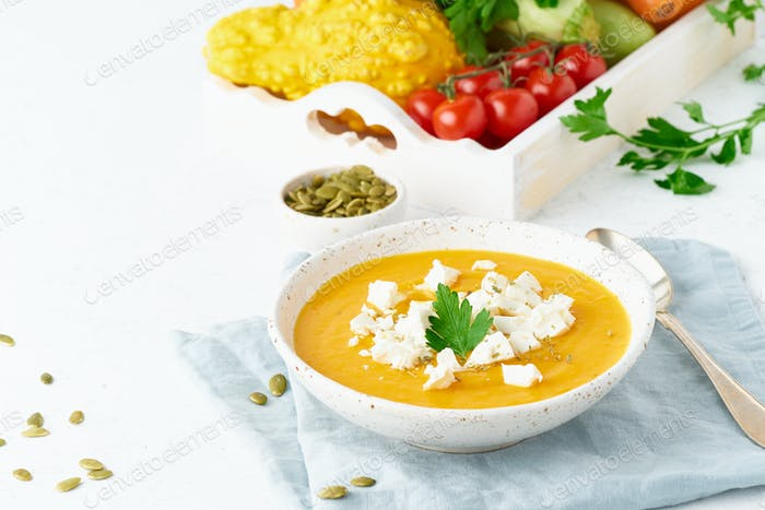 Pumpkin cream soup with feta cheese, autumn homemade food, white background, closeup, copy space