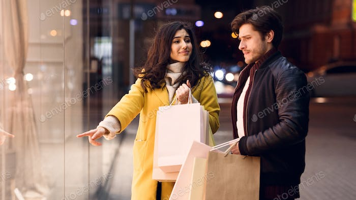 Please, buy! Woman asking boyfriend to buy clothes