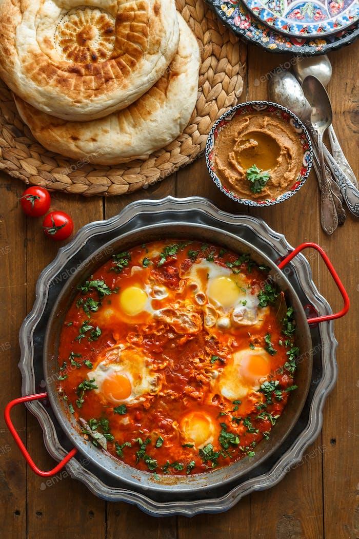 Leckeres Frühstück Shakshuka in einer eisernen Pfanne. Spiegeleier mit Tomaten, Gesundes Essen.