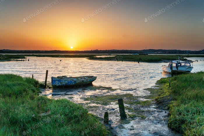 Summer sunrise over old boats on the shores of Holes Bay
