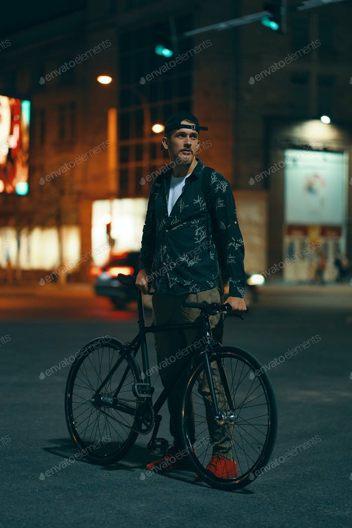 Cyclists standing on the road aside his classic bike while watching night city