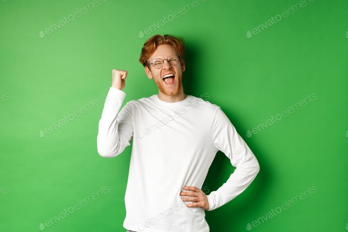 Young cheerful guy scream of joy, winning prize and celebrating, making fist pump gesture and