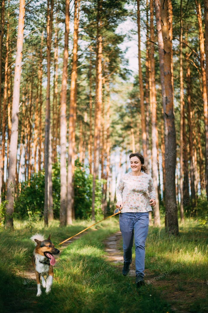 Active Young Adult Caucasian Woman Running With Pet Dog In Summe