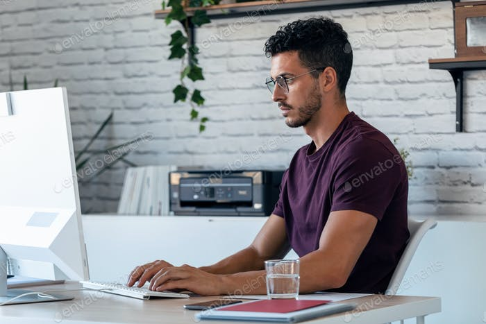 Handsome young entrepreneur working with the computer in the office.