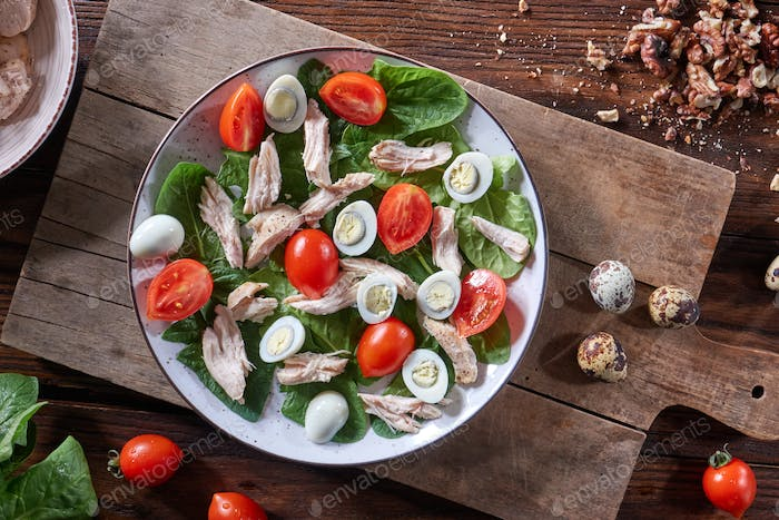 Healthy freshly prepared salad of quail eggs, meat, tomatoes and spinach in a plate on a wooden