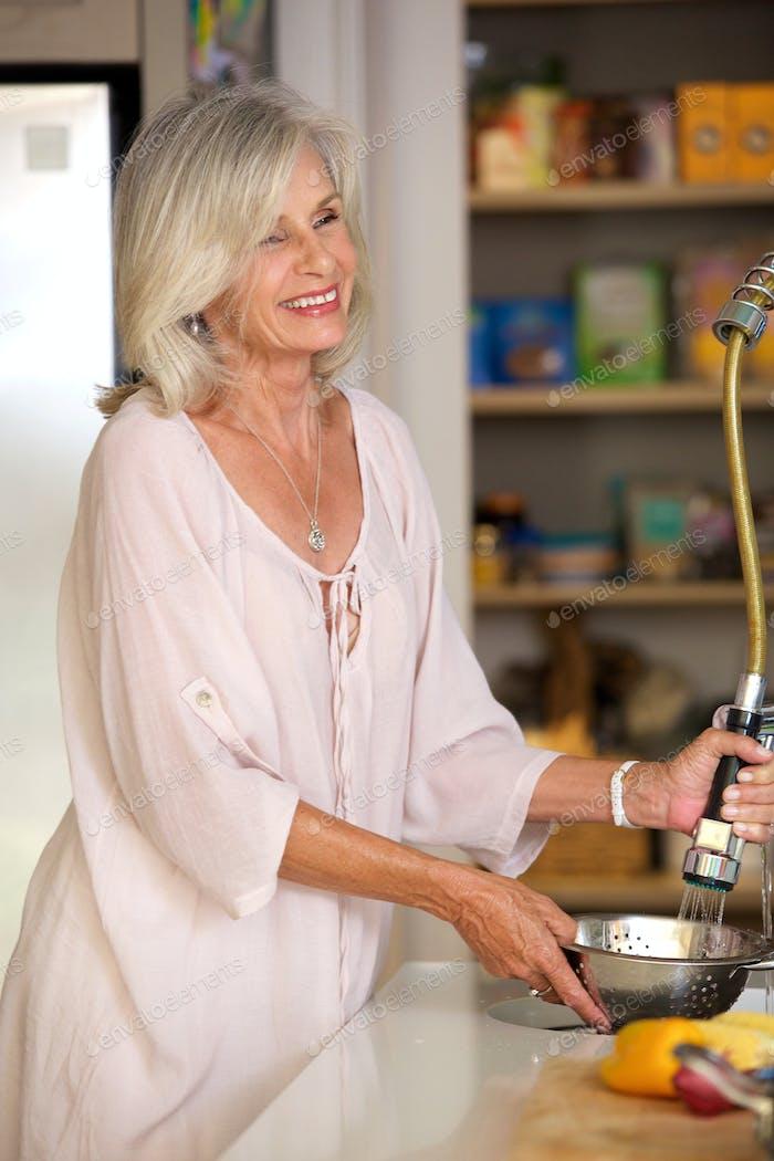 smiling older woman washing vegetables in kitchen