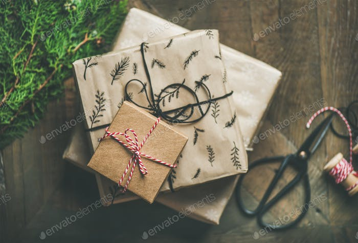 Gift boxes, fur tree branches, rope, scissors over wooden background