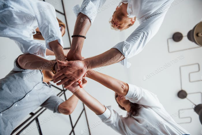 View from below. Successful business people putting their hands together