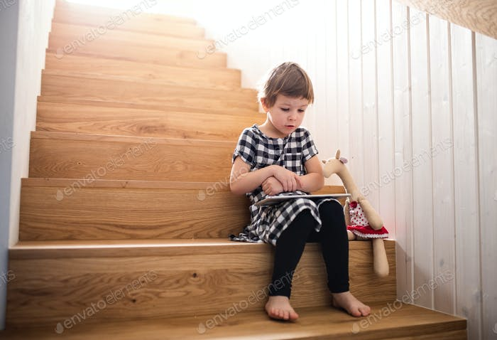 A small girl sitting indoors on the stairs, using tablet.